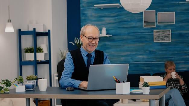 Victo를 몸짓으로하는 스타트 업 회사를 위해 집에서 일하는 노트북에 대한 좋은 소식을받는 행복한 노인 관리자