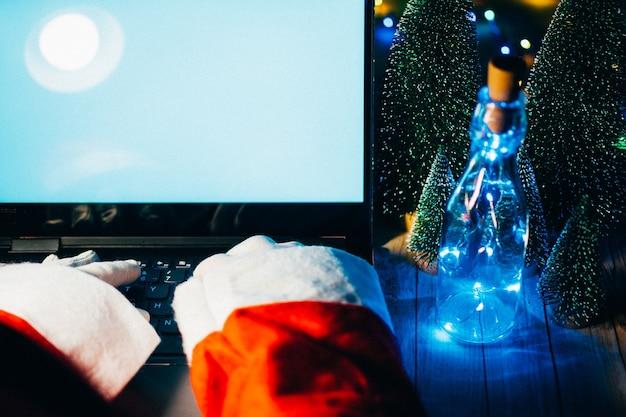 메리 크리스마스 이브에 늦은 시간에 워크샵 홈 테이블에 앉아 랩톱 컴퓨터를 사용하여 선물 상자를 들고 모자를 쓴 행복한 늙은 산타클로스. 전자 상거래 웹 사이트 크리스마스 시간 휴일 온라인 쇼핑 전자 상거래 판매