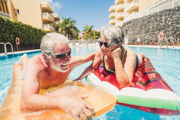 幸せな古い年配の白人カップルは、色付きのリロと一緒にプールで泳いで、一緒に楽しんで夏のレジャー活動を楽しんでいます