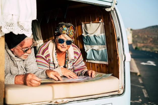 幸せな老夫婦は古い車のビンテージバンで一緒に旅行を楽しんでいます