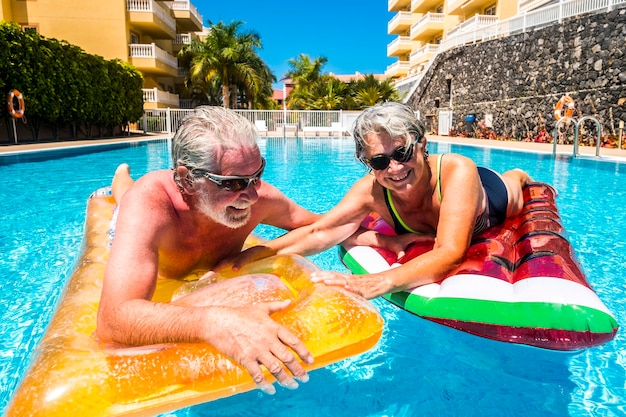 Happy old senior people couple enjoy the summer and have fun with coloured lilos together inthe wimming pool