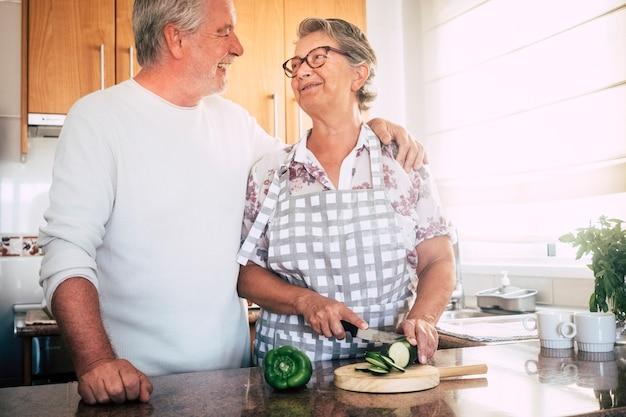 Счастливые пожилые пенсионеры с красивыми белыми волосами пара людей вместе готовят дома на кухне, режут овощи для концепции здорового образа жизни
