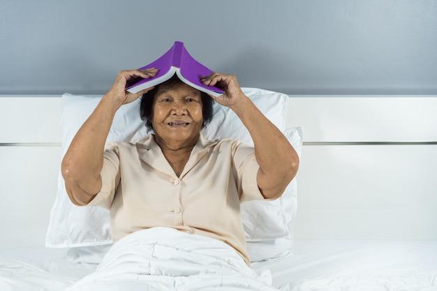 그녀의 머리에 책을 들고 침대에서 행복 한 늙은 여자