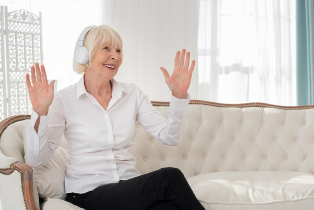 Happy old woman sitting on sofa with headphones
