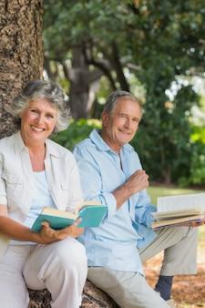 함께 카메라를보고 나무 줄기에 앉아 책을 읽고 행복 세 커플
