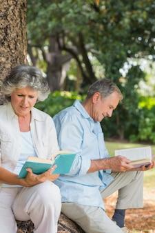 함께 나무 줄기에 앉아 책을 읽고 행복 세 커플