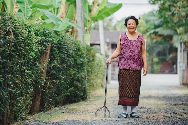 Happy older grandmother walk with cane.