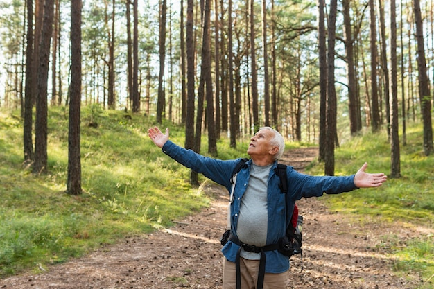 Happy older man exploring nature with backpack