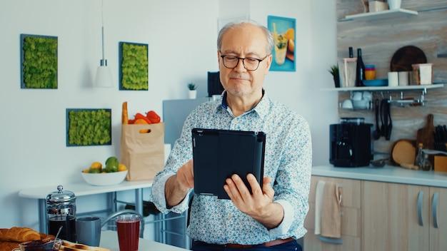 태블릿 pc를 사용하여 아침 식사를 하는 동안 부엌에서 행복한 노인. 모바일 앱, 터치스크린이 있는 현대적인 인터넷 온라인 정보 기술을 사용하는 퇴직 연령에 태블릿 휴대용 패드 pc를 사용하는 노인