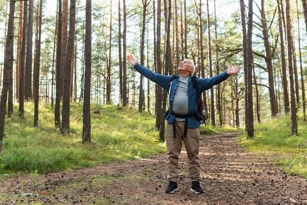 Счастливый пожилой мужчина с распростертыми объятиями на природе