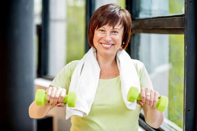 窓の背景に屋内でダンベルとスポーツウェアのトレーニングで幸せな年上の女性