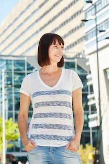 Happy older woman in striped t-shirt standing outside