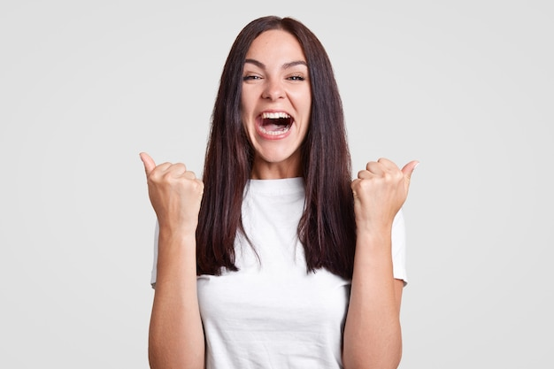Happy onjoyed brunette female clenches fists in triumph, finds out about pregnancy, going to share this wonderful news with husband, dressed in white outfit. people and achievement concept