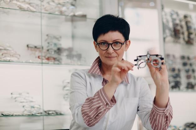 Счастливый оптик, выбирая очки, женский оптометрист в очках.