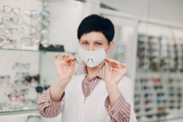 Счастливый оптик в медицинской маске для лица, выбирая очки, женский оптометрист в очках.