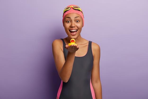 水着姿の幸せな楽観的な暗い肌の女性は泳ぎながら喜びを持っています