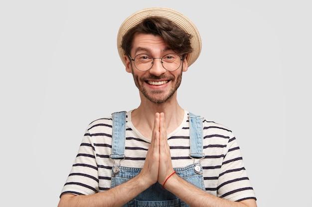 カジュアルな服装と麦わら帽子をかぶった幸せな楽観的な男性農家は、前向きな笑顔を持ち、祈りのジェスチャーで手を保ち、白い壁に隔離された望ましいものを求めます。人と信仰の概念