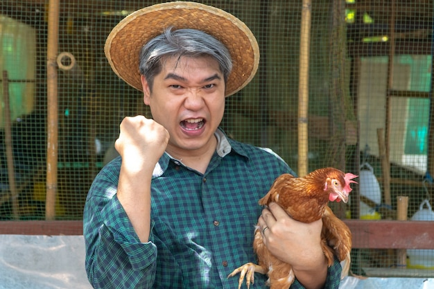 Happy organic middle aged farmer hold chicken in his arms in front of hen house in countryside.
