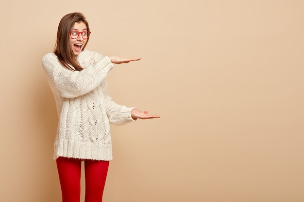 幸せな感情に訴える女性は、大きなジェスチャー、両手で形を示し、驚きと喜びを表現し、眼鏡、走り幅跳び、赤いタイツを身に着け、ベージュの壁に隔離されています。巨大なサイン。