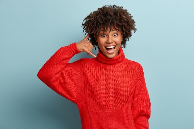Happy overjoyed afro american woman shows call me gesture, asks keep in touch, wears warm red sweater, being in high spirit, isolated over blue wall. people and body language concept.