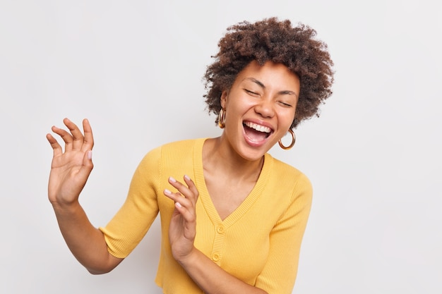 Happy overjoyed curly haired afro american woman dances and smiles carefree keeps eyes closed dressed in casual yellow jumper isolated over white wall Free Photo