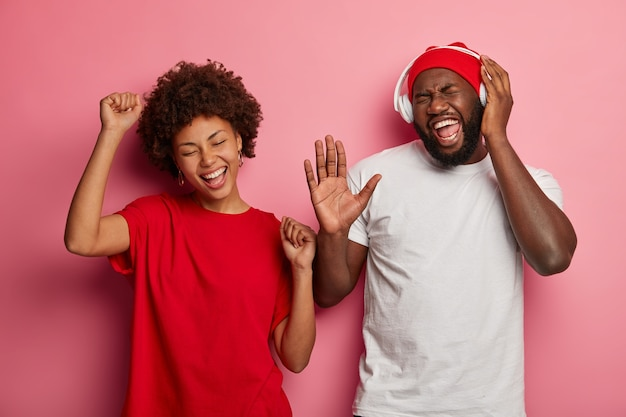 Happy overjoyed dark skinned curly man and woman dance actively while listen music via headphones, keep hands raised and eyes closed from joy, isolated on pink wall.