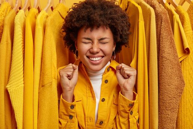 Felice donna dalla pelle scura felicissima sta vicino a vestiti eleganti gialli su grucce, stringe i pugni, si rallegra dell'acquisto riuscito