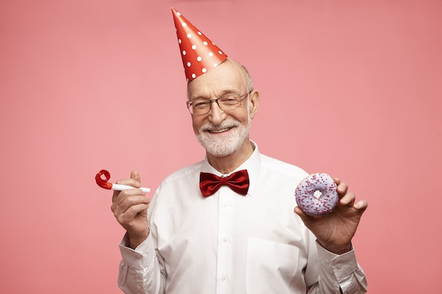 Happy overjoyed ecstatic mature seventy year old man with red cone hat