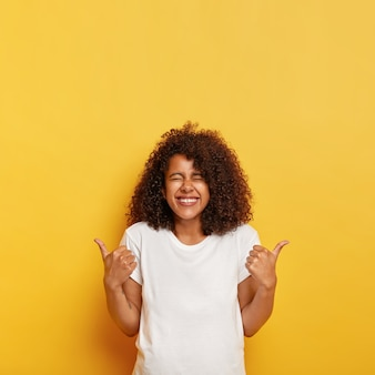 Happy overjoyed ethnic lady with bushy crisp hair gives positive answer with thumbs up, likes awesome idea, closes eyes from laugh, dressed in mockup t shirt, isolated on yellow  wall.
