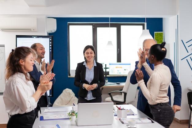 会議のブリーフィングで拍手して立っている幸せな大喜びの金融スタートアップチーム