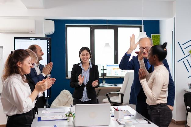 박수를 치고 서 있는 행복한 금융 스타트업 팀