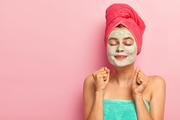 Happy overjoyed woman applies facial clay mask, has rejuvenation treatment, clenches both fists, wears towel, keeps eyes closed, isolated on pink studio wall