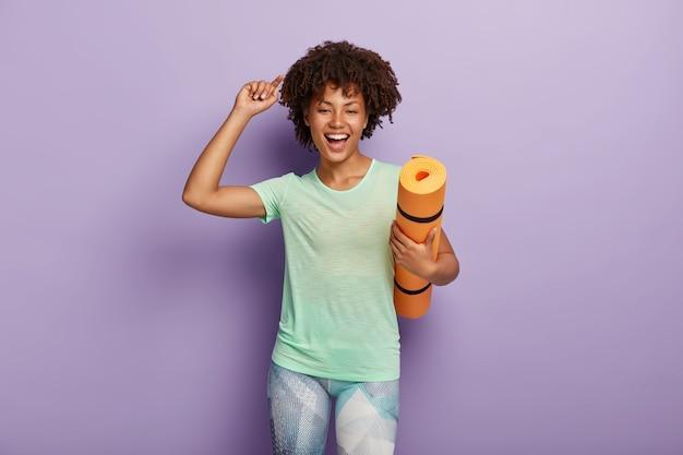 행복하고 기뻐 한 여자가 요가 매트를 들고 팔을 들어 캐주얼 티셔츠와 레깅스를 입고 활동적인 운동에 만족합니다.