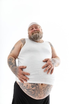 Happy overweight man with big belly and tattoos in sports wear is holding his stomach