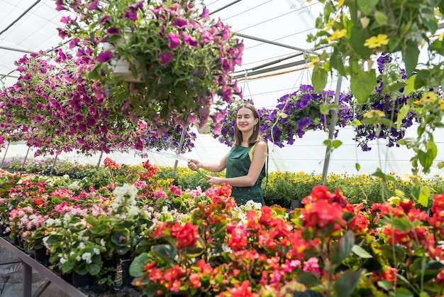 Happy  owner of a flower farm watering and taking care flowers