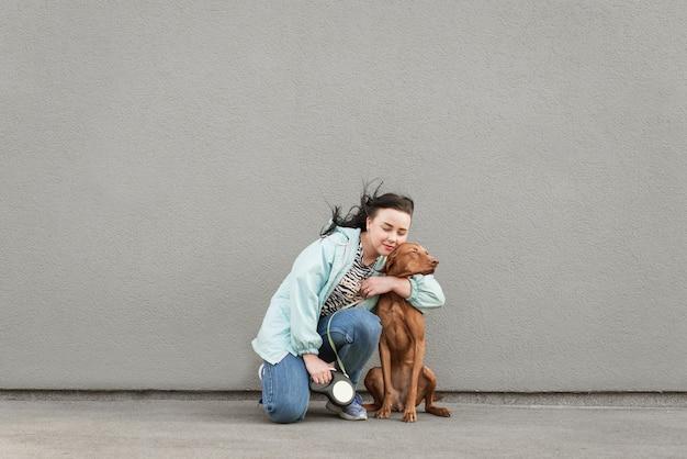 幸せな飼い主が美しい犬を抱きしめる