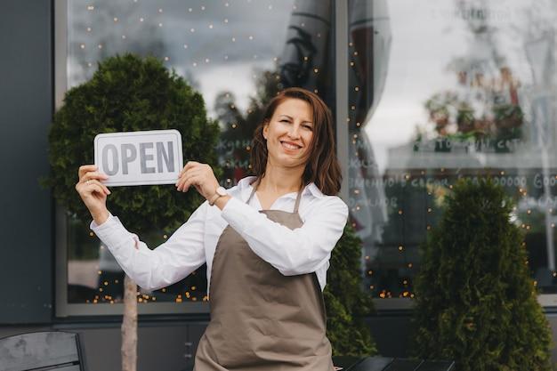 エプロンのカフェの幸せな所有者は、カフェの近くに開いた看板を持って、カメラを見ています。女性ウェイター。