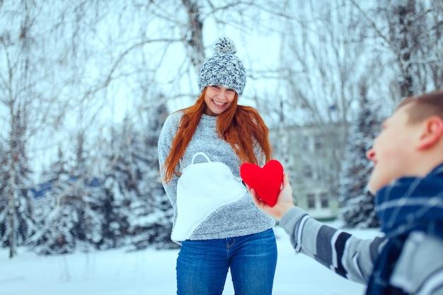 Счастливая пара мужчины и женщины обнимаются и веселятся в теплой одежде на улице