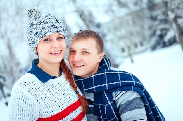 따뜻한 옷을 입고 밖에서 껴안고 즐거운 시간을 보내는 행복한 남녀