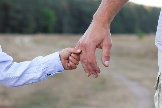 The happy parent holds the hand of a small child