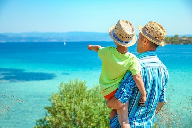 Счастливый родитель с ребенком на берегу моря греция на открытом воздухе