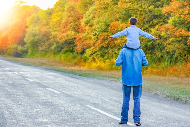 A happy parent with a child in the park hands on nature travel go along the road