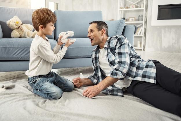幸せな親子関係。ハンサムな警告黒髪の父は笑顔で息子とおもちゃを持って遊んでいます