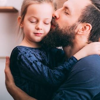 행복한 육아. 그의 귀여운 작은 딸에 게 사랑과 관심을 보여주는 아버지의 초상화.