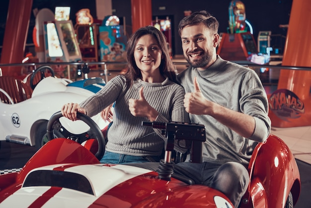 Happy parents in amusement park sitting on toy car