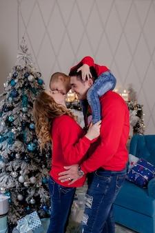 Счастливые родители и ребенок возле елки дома. гостиная украшена елкой и подарочной коробкой. новогодняя тема.