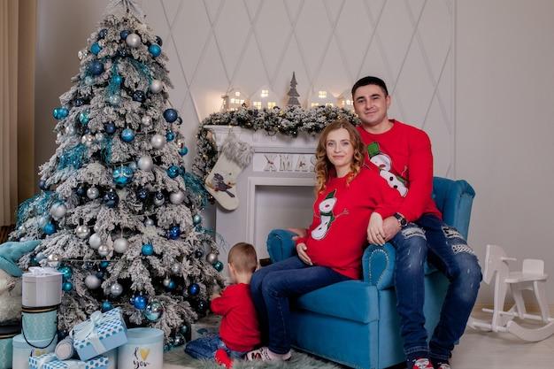 Счастливые родители и ребенок возле елки дома