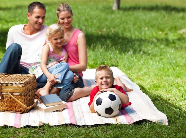 幸せな親と子供たちが公園でピクニックをする
