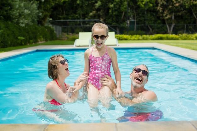 행복 한 부모와 딸이 수영장에서 재미