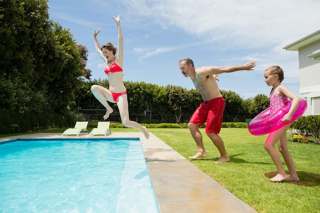 幸せな親と娘がプールでジャンプ